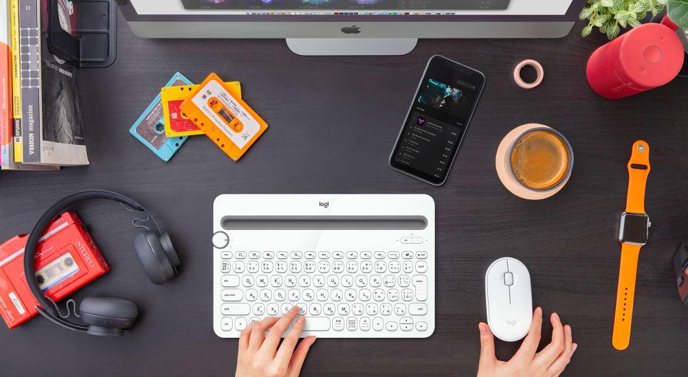 デスク上のホワイトのキーボードとマウス、appleパソコンとiPhone