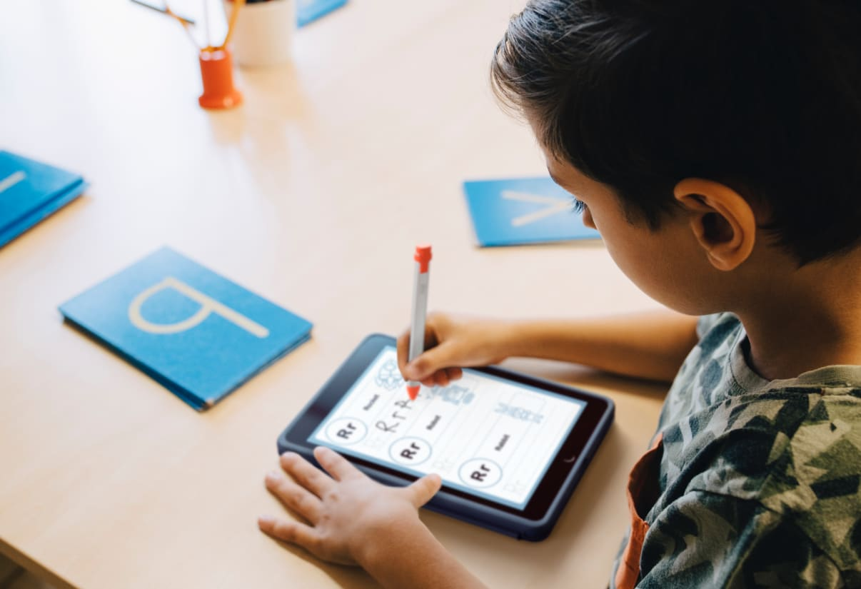 Un élève écrivant sur une tablette avec un stylet Crayon orange.