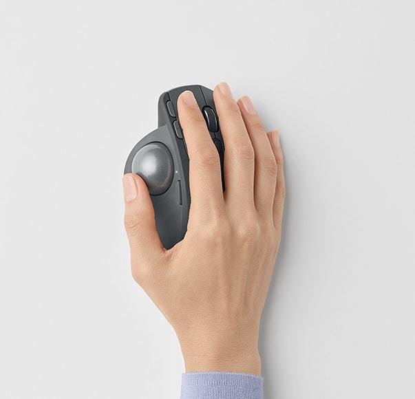 一隻手握著 MX Ergo 軌跡球滑鼠