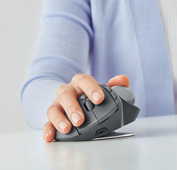 Una mano sostiene un ratón trackball MX Ergo