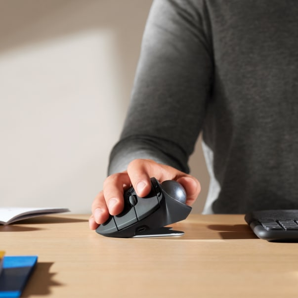 A hand holding a MX Ergo trackball mouse