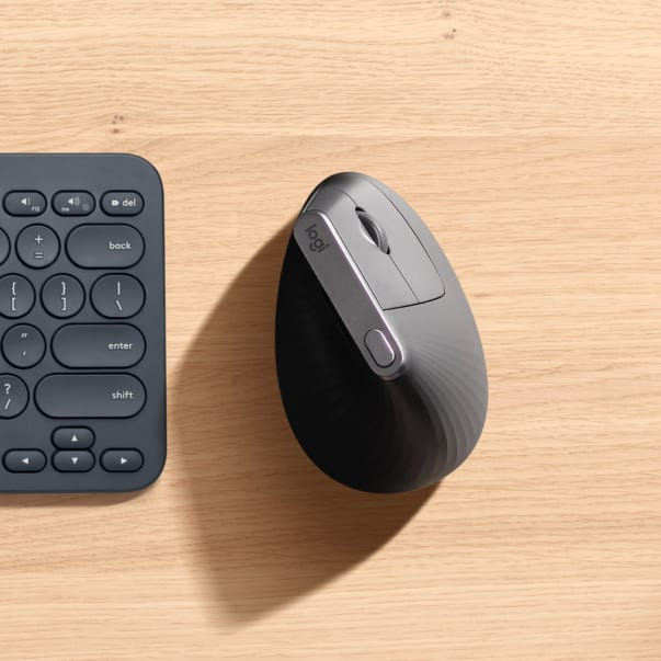Vertical mouse on table next to keyboard