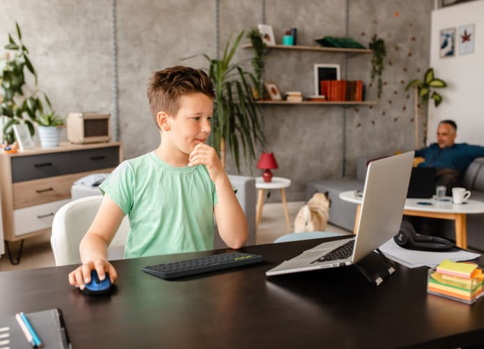 A boy sitting at a desk and looking at his laptop.