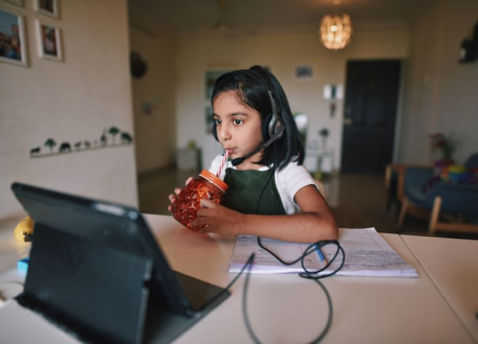 Girl having drinks and learning using wired headset