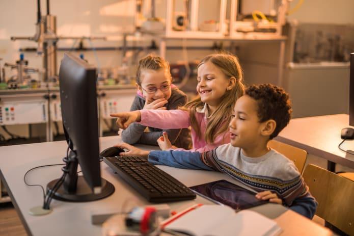3 barn som bruker tastatur og mus