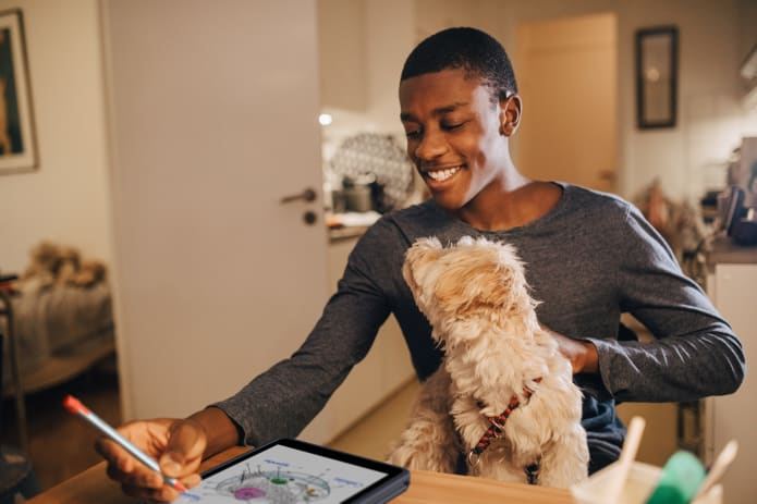 Leerling met hond tekenend op iPad met digitaal potlood