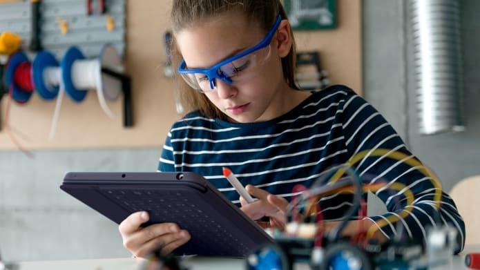 Une jeune élève tenant Crayon et regardant une tablette.