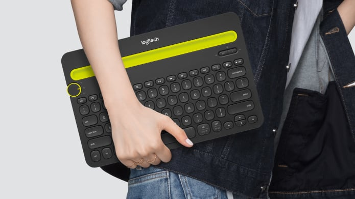 Person holding gray keyboard with yellow accents